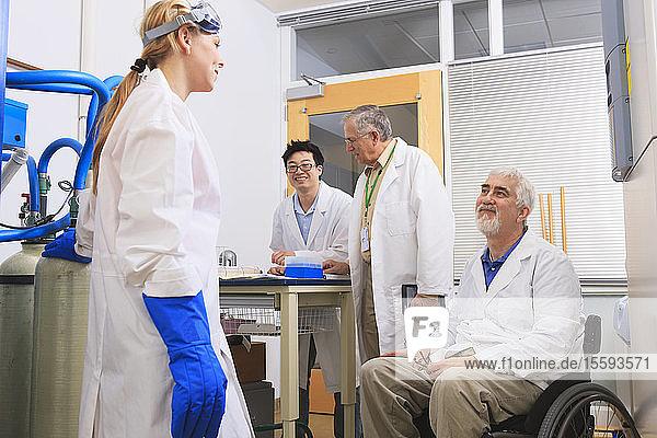 Professor mit Muskeldystrophie bespricht mit einem Ingenieurstudenten und einem Professor das Logbuch für ein Wasserdestillationssystem in einem Labor
