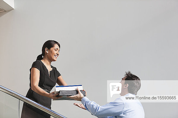 Business couple passing folders on stairs of office building