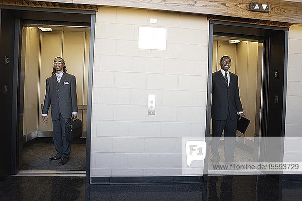 Young businessmen standing in elevators.