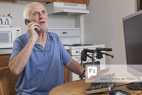 Man with Ataxia talking on his cell phone at the computer in the kitchen