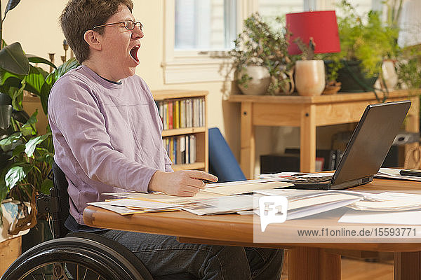 Businesswoman with multiple sclerosis in a wheelchair tired of doing her paperwork