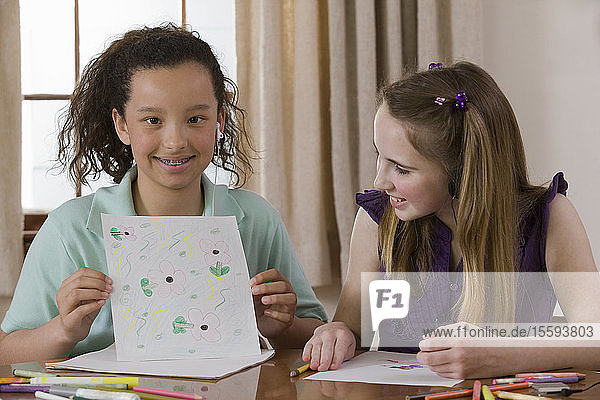 Hispanic girl sitting with her friend and showing a drawing