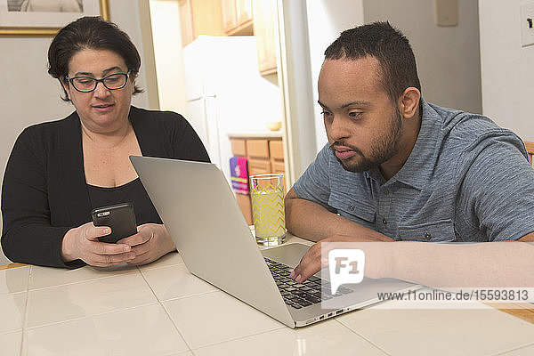 African American man with Down Syndrome using a laptop with his mother at home