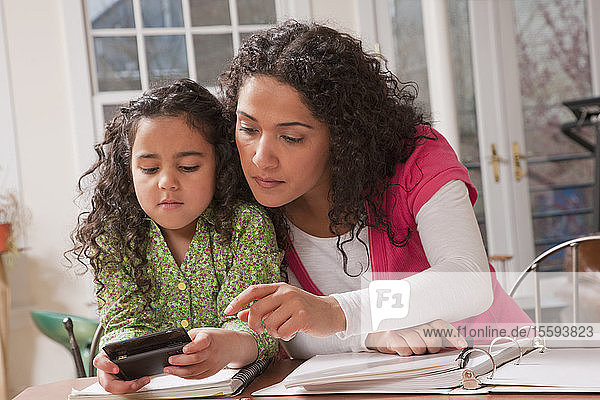 Hispanic woman helping her daughter to send a message on a mobile phone