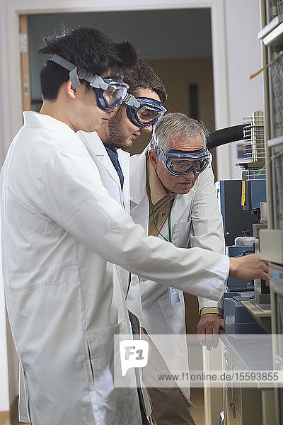 Professor working with engineering students on thermomechanical analysis instrument in a laboratory