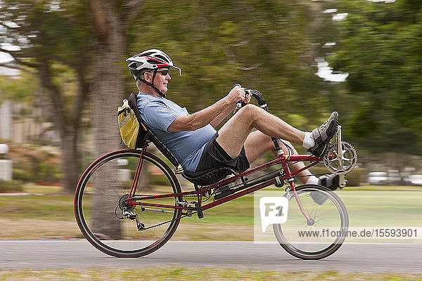 Man riding a recumbent bicycle in a park