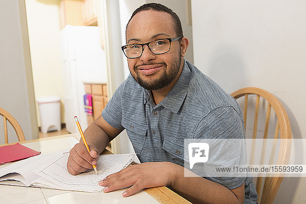 Happy African American man with Down Syndrome doing paperwork at home
