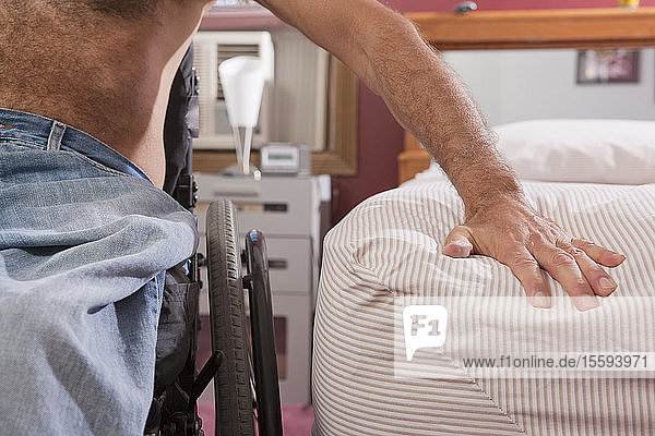 Man with spinal cord injury preparing to get into bed from his wheelchair