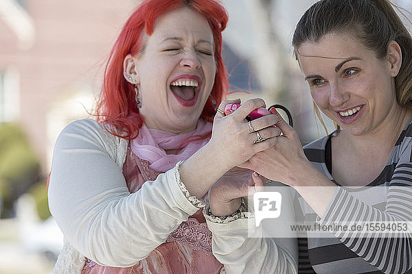 Blind young women using assistive technology on their cell phones and laughing