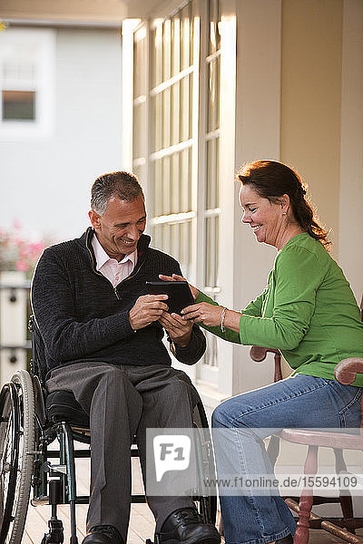 Woman and her husband in a wheelchair in front of their home using a digital tablet
