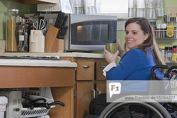 Woman with Spina Bifida in a wheelchair using her microwave in the accessible kitchen