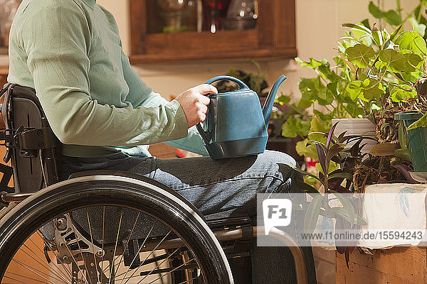 Woman with multiple sclerosis in a wheelchair watering houseplants