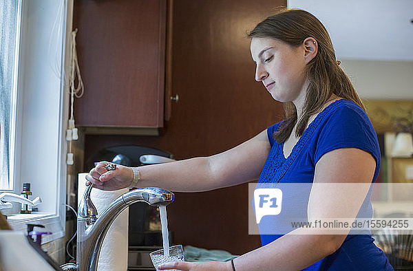 Young Woman with Cerebral Palsy taking a water of glass at home