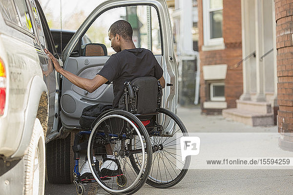 Man in a wheelchair who had Spinal Meningitis entering his accessible vehicle