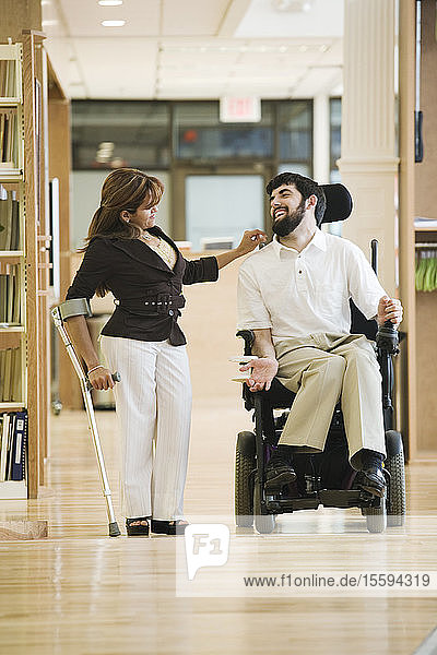 View of a man with Cerebral Palsy and woman conversing.