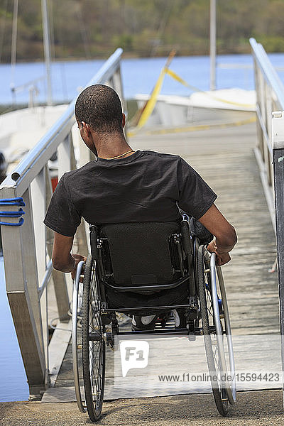 Man in a wheelchair who had Spinal Meningitis going down a ramp to a dock