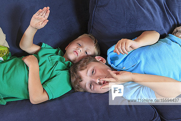 Boys with hearing impairments signing 'water slide' in American sign language on their couch