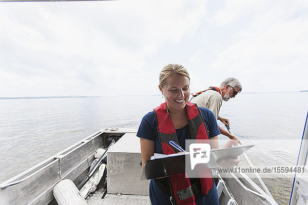 Engineer recording water sample data on board boat in public water supply