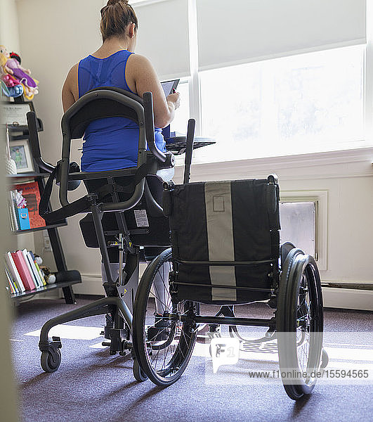 Woman with spinal cord injury working at home at her stand up desk