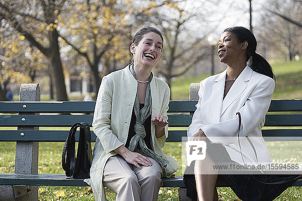 Two women sitting on a bench in the park and laughing.
