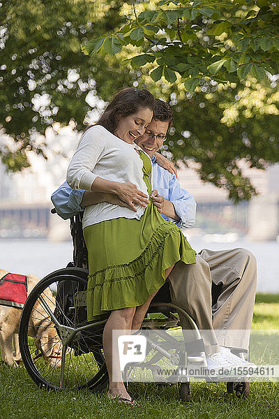 Man with a spinal cord injury in a wheelchair feeling his wife's baby belly