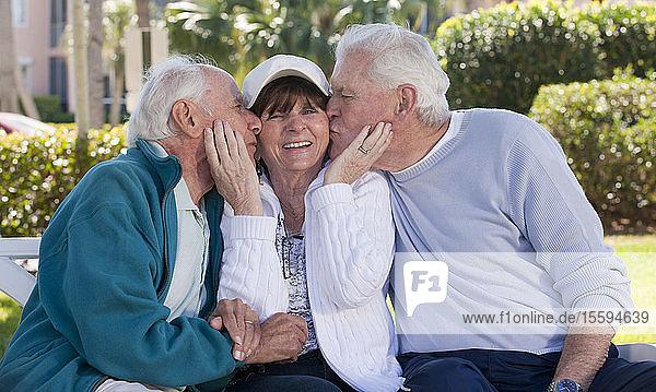 Two senior men kissing their female friend in a park