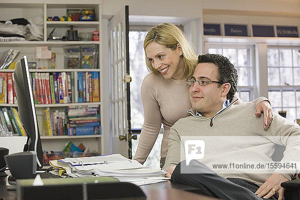 Businesswoman with a Hispanic businessman working on a desktop pc
