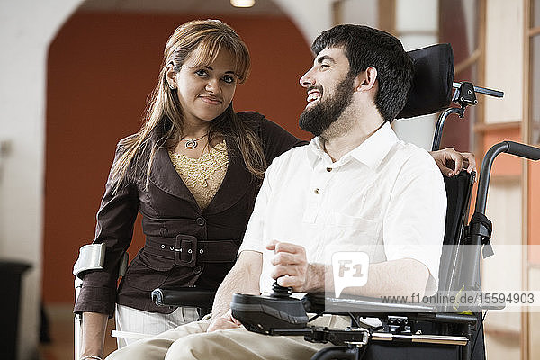 Portrait of a man with Cerebral Palsy and woman smiling.