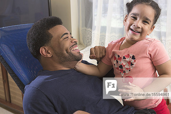 African American man with Cerebral Palsy having fun with his daughter at home