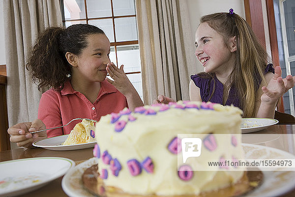 Two girls eating birthday cake and smiling