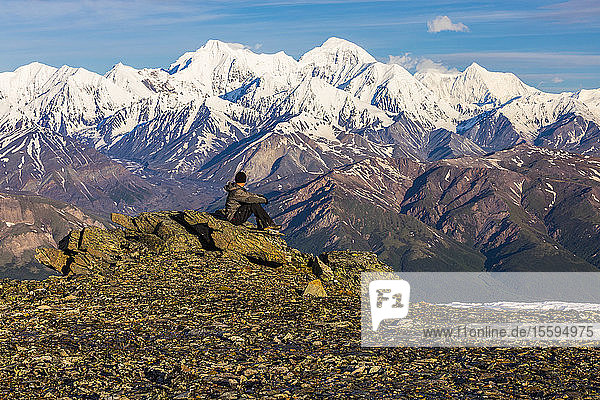 A hiker resting on rocks observes McGinnis Peak  Mount Moffit  and Mount Hayes towering in the distance; Alaska  United States of America