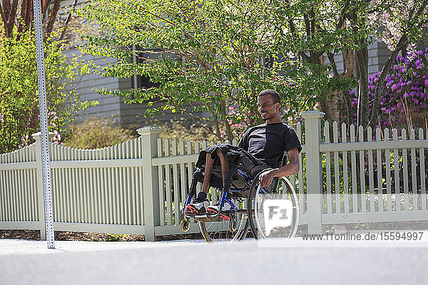 Man in a wheelchair who had Spinal Meningitis in a neighborhood leaning on his wheels
