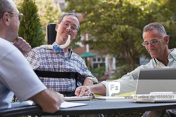 Businessmen with disabilities doing paperwork