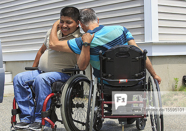 Friends with Spinal Cord Injuries in wheelchairs greeting each other