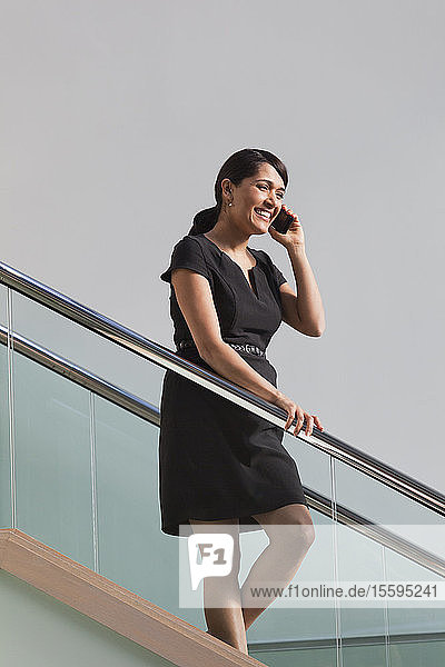 Businesswoman talking on mobile phone walking down stairs