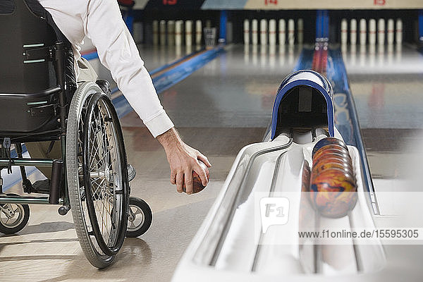 Low section view of a man with a Spinal Cord Injury playing ten pin bowling