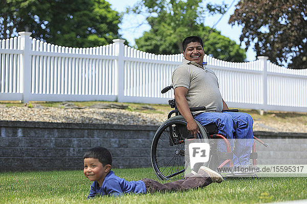 Hispanic man with Spinal Cord Injury in wheelchair playing with his son in lawn