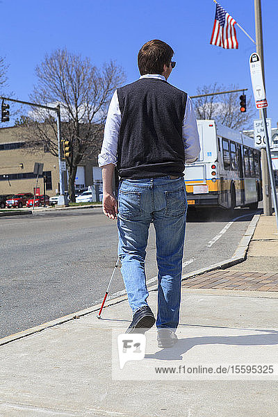 Young blind man with cane heading toward a bus stop