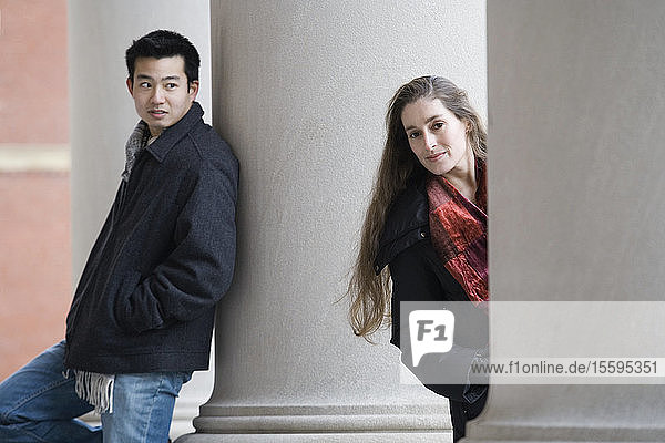 Portrait of a young woman peeking from behind a column and a young man looking at her