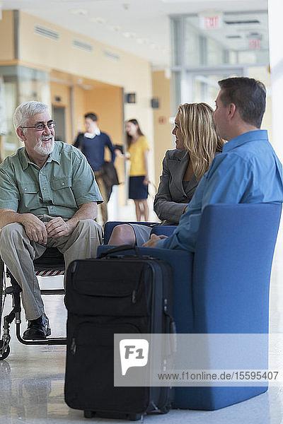 Fluggäste  die sich in einer Flughafenlounge unterhalten  einer davon mit Muskeldystrophie