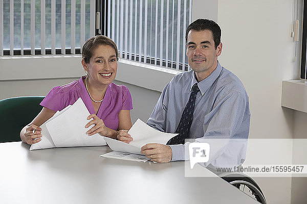 Businesswoman and a businessman with spinal cord injury smiling in an office