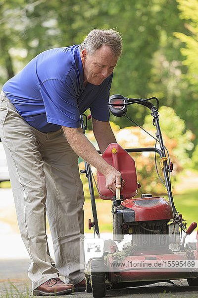 Man with Cerebral Palsy and dyslexia filling his lawn mower with gas