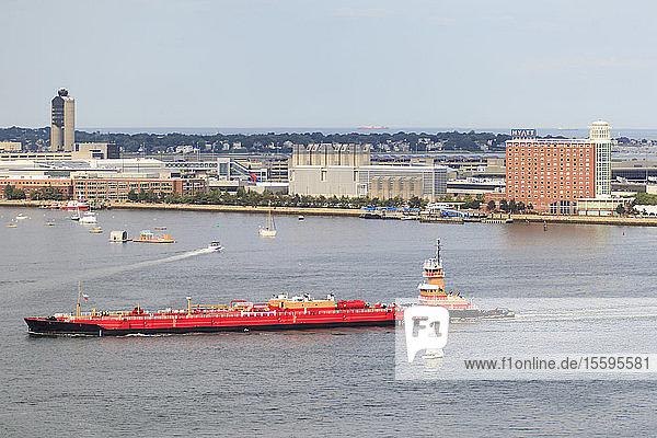 Tugboat moving tanker through Boston Harbor  Logan Airport and East Boston  Boston  Massachusetts  USA