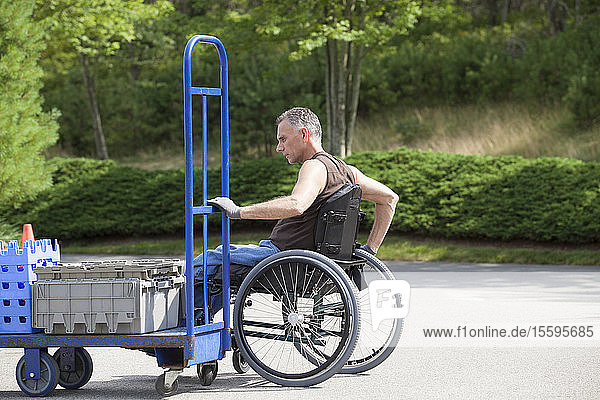 Loading dock worker with spinal cord injury in a wheelchair moving a hand truck