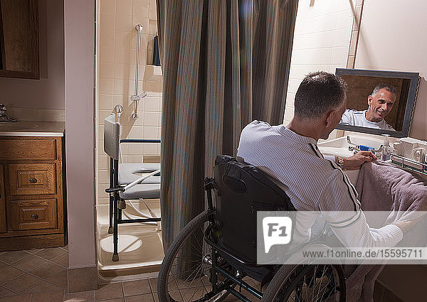 Man with spinal cord injury in a wheelchair using a towel
