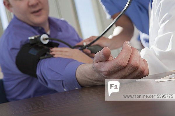 Female doctor and nurse measuring a patient's blood pressure