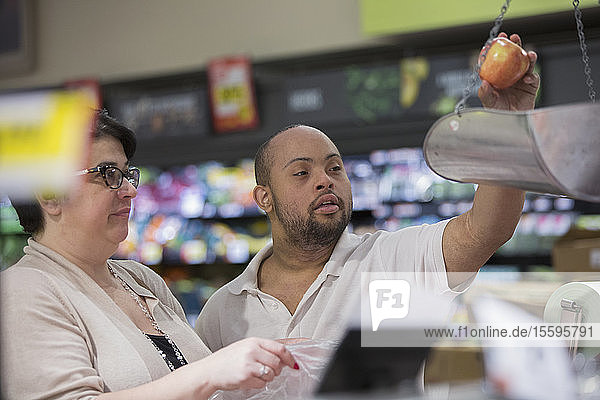 Man with Down Syndrome weighing fruit in a grocery store