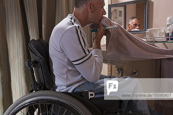Man with spinal cord injury in a wheelchair brushing his teeth