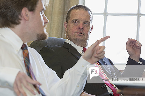 Man with Down Syndrome discussing with a collaborator in the State Capitol in his office