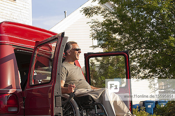 Man in wheelchair with Spinal Cord Injury being lowered from accessible van
